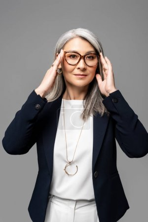 Photo pour Exécutif asiatique femme d'affaires avec des cheveux gris dans des lunettes isolées sur gris - image libre de droit