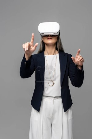 Photo for Corporate businesswoman pointing and using virtual reality headset isolated on grey - Royalty Free Image
