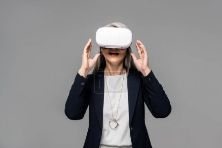 Photo for Attractive surprised businesswoman using virtual reality headset isolated on grey - Royalty Free Image