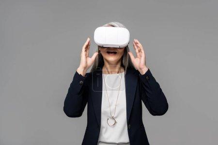 Photo pour Attrayant surpris femme d'affaires en utilisant casque de réalité virtuelle isolé sur gris - image libre de droit