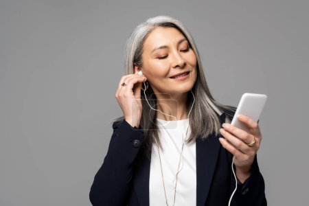 Photo for Smiling asian businesswoman with grey hair listening music with earphones and smartphone isolated on grey - Royalty Free Image