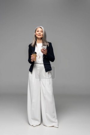 beautiful asian businesswoman with coffee to go listening music with earphones and smartphone on grey