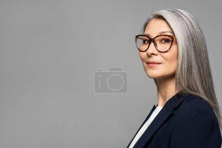 Photo pour Élégante femme d'affaires asiatique aux cheveux gris dans des lunettes isolées sur gris - image libre de droit