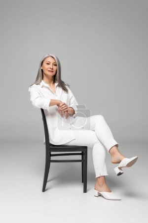 Photo for Beautiful confident asian woman with grey hair sitting on chair on grey - Royalty Free Image