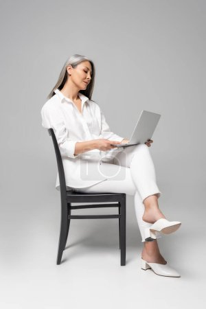 adult attractive asian woman with grey hair sitting on chair and using laptop on grey
