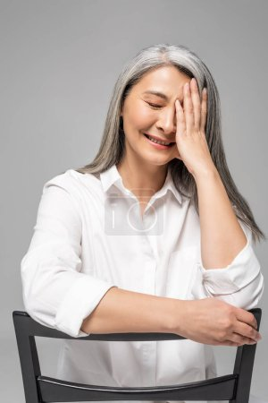 Foto de Hermosa riendo asiático mujer con gris pelo sentado en silla aislado en gris - Imagen libre de derechos