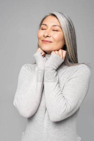 sourire asiatique femme à col roulé avec les cheveux gris et les yeux fermés isolé sur gris