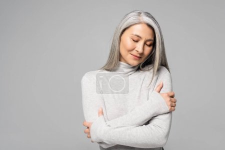 Photo for Dreamy asian woman in turtleneck with grey hair and closed eyes isolated on grey - Royalty Free Image
