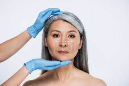 Photo pour Médecin en latex gants toucher visage de attrayant nu asiatique femme isolé sur gris - image libre de droit