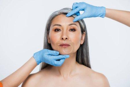 Photo pour Médecins en latex gants toucher le visage de nu asiatique femme avec des cheveux gris isolé sur gris - image libre de droit