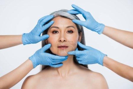 Photo pour Médecins en latex gants toucher visage de nu asiatique femme isolé sur gris - image libre de droit