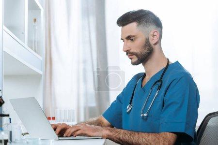 Photo pour Jeune médecin avec stéthoscope sur la dactylographie du cou sur ordinateur portable - image libre de droit