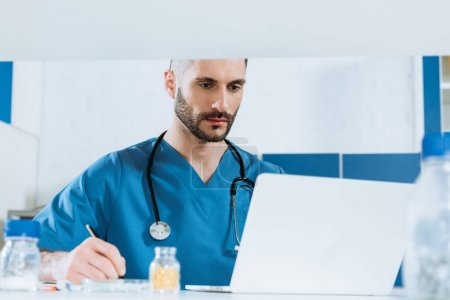 selective focus of young doctor writing while looking at laptop