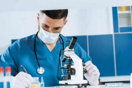 Photo for Selective focus of young biologist in medical mask and latex gloves writing near microscope in lab - Royalty Free Image