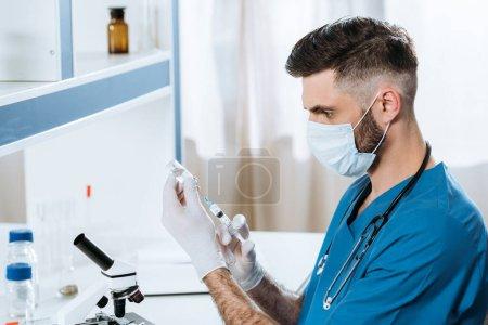 Photo pour Jeune biologiste en masque médical et gants en latex prenant des médicaments avec seringue - image libre de droit