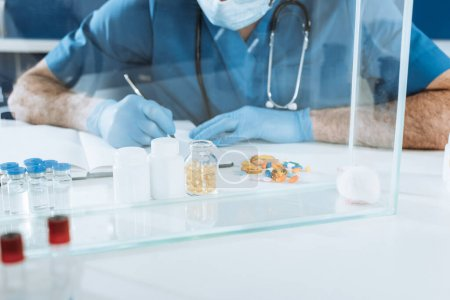 Photo for Cropped view of veterinarian in medical mask and lates gloves writing near containers with medicines and white mouse in glass box - Royalty Free Image