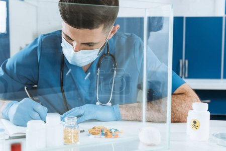 Photo for Young veterinarian in medical mask and lates gloves writing near containers with medicines and white mouse in glass box - Royalty Free Image