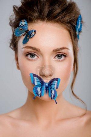 Photo pour Belle jeune femme avec des papillons décoratifs sur le visage isolée sur le gris - image libre de droit