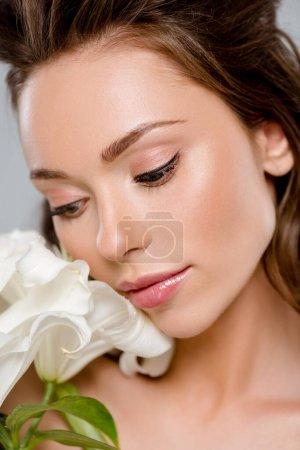 Photo pour Jolie femme regardant des fleurs blanches isolées sur gris - image libre de droit