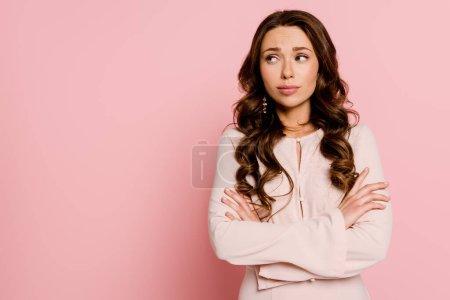 Photo pour Fille insatisfaite debout avec les bras croisés sur rose - image libre de droit