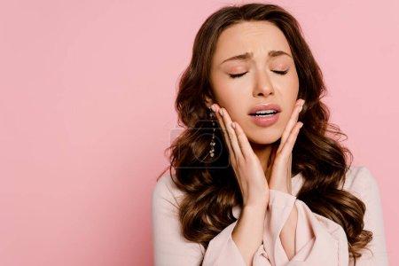 Photo pour Femme inquiète avec les yeux fermés toucher visage isolé sur rose - image libre de droit