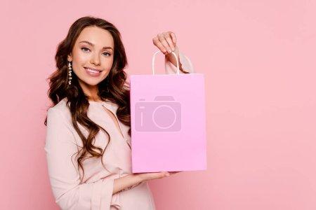 Photo pour Une jeune femme souriante tenant un sac isolé sur du rose - image libre de droit