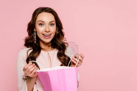 happy young woman holding shopping bag isolated on pink