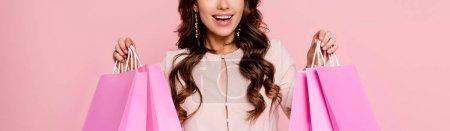 Foto de Foto panorámica de la joven feliz sosteniendo bolsas aisladas en rosa - Imagen libre de derechos