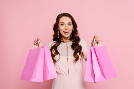 Photo for Excited young woman holding shopping bags isolated on pink - Royalty Free Image