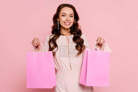 Photo pour Heureuse jeune femme tenant des sacs à provisions isolés sur rose - image libre de droit