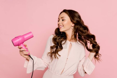 Photo pour Joyeuse jeune femme utilisant sèche-cheveux isolé sur rose - image libre de droit