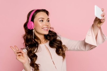 Photo pour Fille heureuse dans les écouteurs sans fil prenant selfie et montrant signe de paix isolé sur rose - image libre de droit