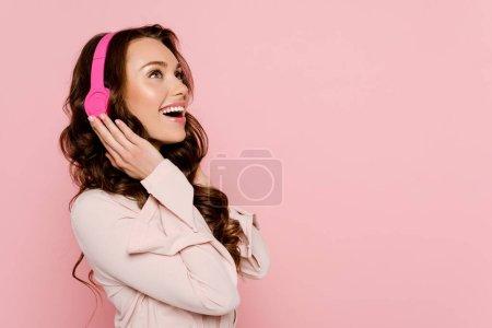 Photo pour Femme excitée écouter de la musique dans des écouteurs sans fil isolés sur rose - image libre de droit