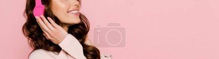Photo pour Plan panoramique de fille joyeuse écoutant de la musique dans des écouteurs sans fil isolés sur rose - image libre de droit