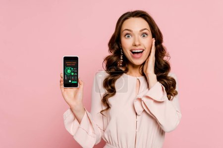 Photo for Excited girl holding smartphone with charts and graphs on screen and looking at camera isolated on pink - Royalty Free Image