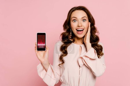Photo for Excited girl holding smartphone with trading courses on screen and looking at camera isolated on pink - Royalty Free Image