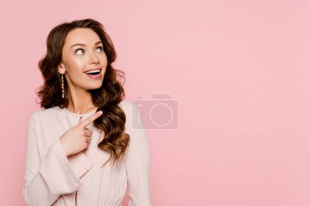 Photo for Excited woman pointing with finger and looking away isolated on pink - Royalty Free Image