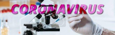 Foto de Vista parcial del biólogo en guantes de látex con jeringa cerca del microscopio, inyección panorámica, ilustración del coronavirus - Imagen libre de derechos