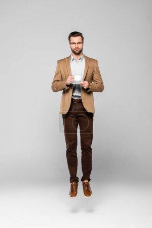 Photo pour Bel homme d'affaires lévitant et tenant une tasse de café sur gris - image libre de droit