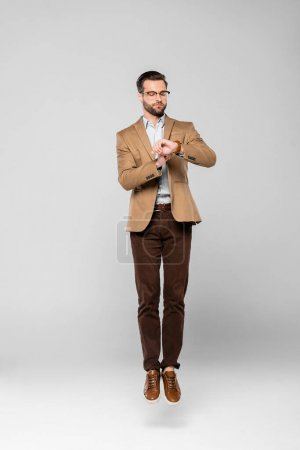 Photo for Handsome businessman levitating and looking at watch on grey - Royalty Free Image