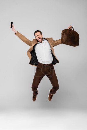 Photo for Excited businessman holding smartphone with blank screen and bag while levitating on grey - Royalty Free Image