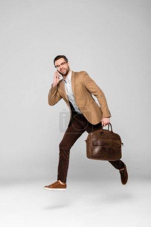 Photo pour Homme d'affaires heureux parlant sur smartphone et tenant sac tout en lévitant sur gris - image libre de droit