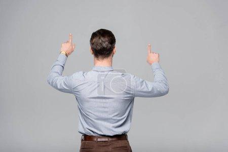 Photo pour Vue arrière de l'homme d'affaires pointant avec les doigts isolés sur gris - image libre de droit