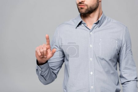 cropped view of bearded businessman pointing with finger isolated on grey