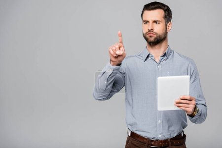 handsome businessman pointing with finger and holding digital tablet isolated on grey