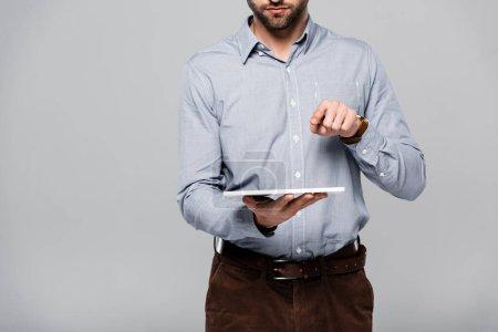 Photo pour Vue recadrée d'un homme d'affaires barbu pointant du doigt et tenant une tablette numérique isolée sur gris - image libre de droit