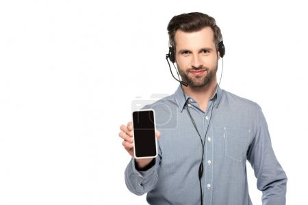 Photo for Handsome operator in headset holding smartphone with blank screen isolated on white - Royalty Free Image