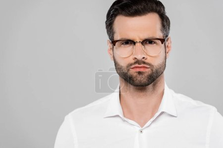 Photo for Bearded and handsome businessman in glasses looking at camera isolated on grey - Royalty Free Image
