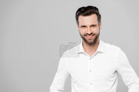 smiling businessman in white shirt looking at camera isolated on grey