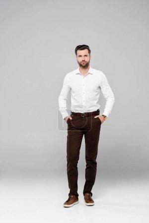 Photo pour Homme d'affaires barbu dans des lunettes debout avec les mains dans les poches sur gris - image libre de droit